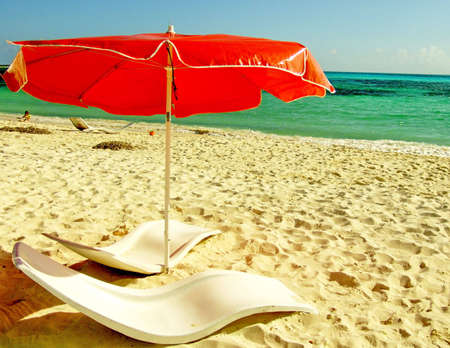 A perfect beach scene: empty sun chairs with red umbrella. Mexico, Cozumel, Punta Sur Park photo