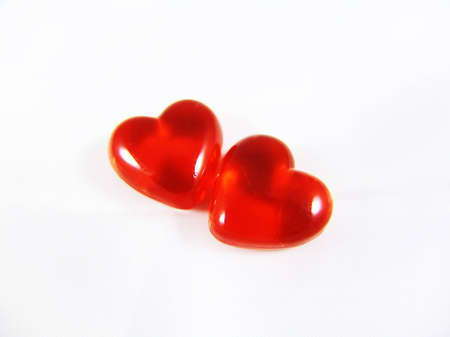 Two red three-dimensional hearts isolated on white background