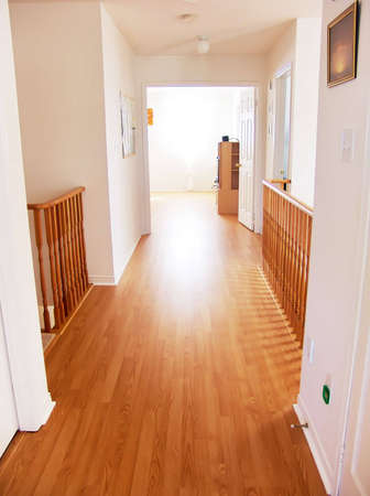 laminate flooring: Empty Corridor in New House leading to bright light window