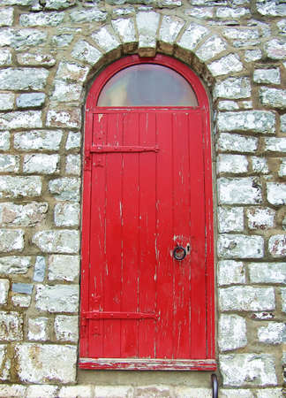 Wooden red door on old stone wall. Stock Photo