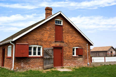 Obsolete brick barn with wooden red doors.  Bluy sky and green grass. 스톡 콘텐츠