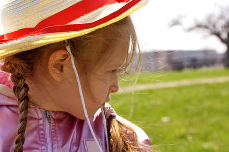 Little girl with hat at park. Blur  background. Spring time.