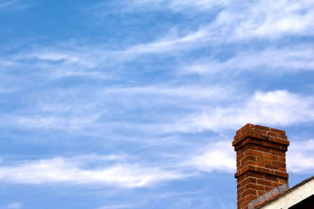 Red brick chimney on blue sky backgroung 스톡 콘텐츠