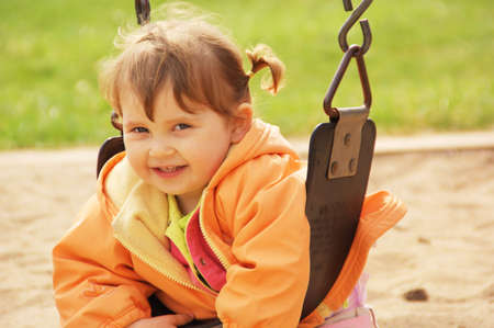 Little girl smiling and swinging on park playground. Spring time.