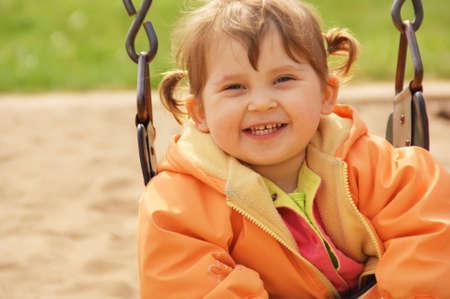 Yong girl laughing at park playground. Spring time.