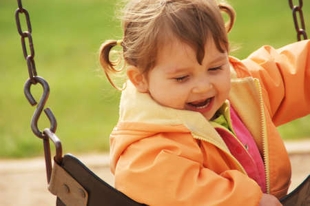 Toddler girl laughing on park playground. Green grass  background. Spring time.