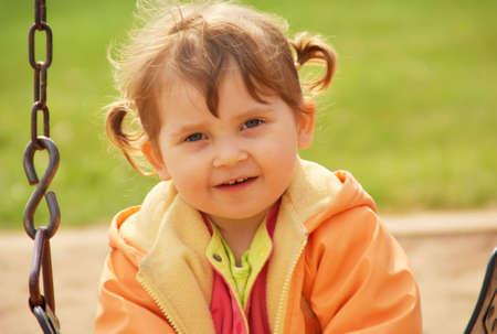 공원 놀이터에서 어린 소녀입니다. 녹색 잔디 배경입니다. 봄 시간.
