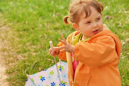 우산을 공원에서 놀고 소녀입니다. 녹색 잔디 배경입니다. 봄 시간.
