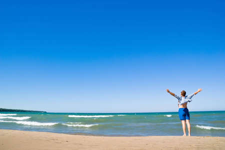 Man with  arms outstretched standing on the lakeshore and  looking up. Sand beach and blue water. Summer, vacation. Stock Photo