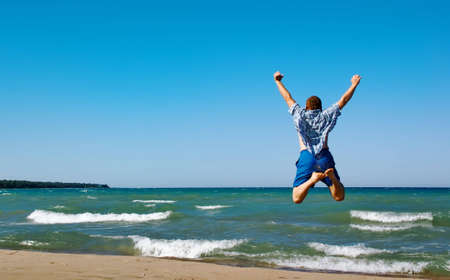 Happy man jumping over sea. Sand beach and blue water. Summer, vacation. Standard-Bild