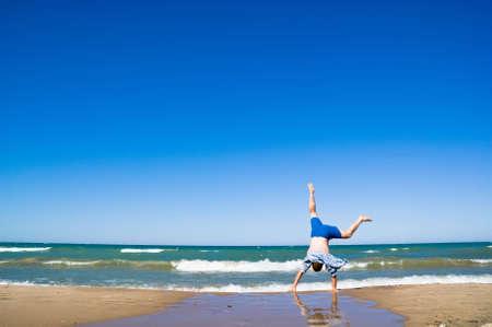 해피 남자 바다 위로 점프입니다. 모래 해변과 푸른 물입니다. 여름 방학.