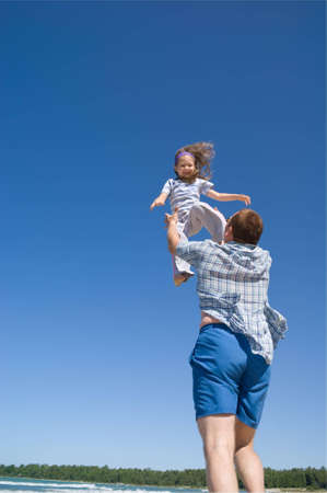 A father throws his little girl into the air