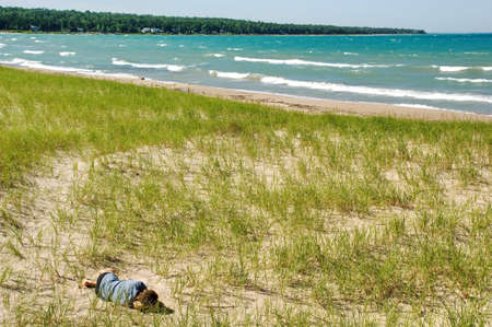 Man dreaming on dune. Vacation, summer time.