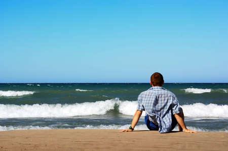 Man sitting on lakeshore and  looking on waves. Sand beach, blue water and wind. Huron lake, Ontario, Canada. Summer, vacation.