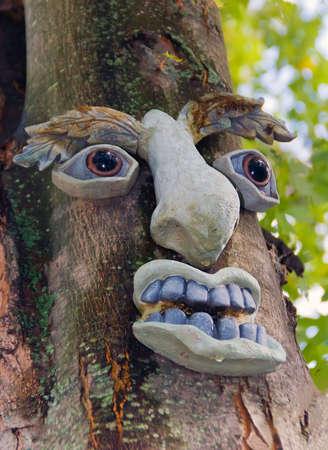 Tree Spirit. Human face decoration on the tree.