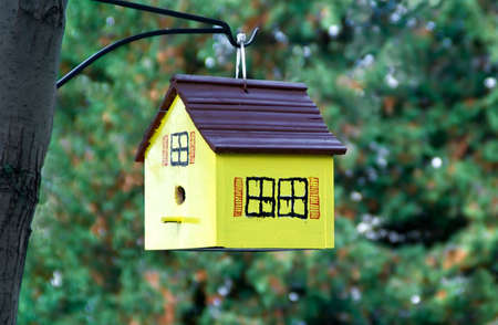 A birdhouse hanging off a tree. Stock Photo