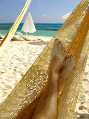 Man relaxing in a hammock on a beautiful sand beach. Cozumel, Mexico, Caribbean Sea. Standard-Bild