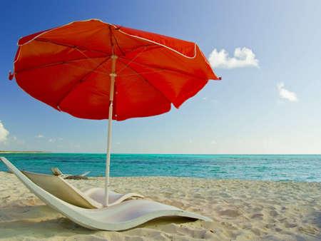 목가적 인 모래 해변에 빨간 해변 우산입니다. 멕시코, Cozumel, Punta Sur. (Reserva Ecologica Parque Punta Sur)