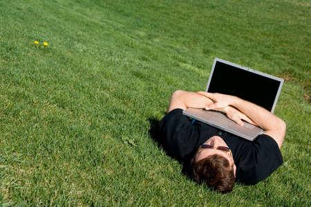Man liggen op het gras met laptop. 21e eeuwse levens stijl.  Stockfoto