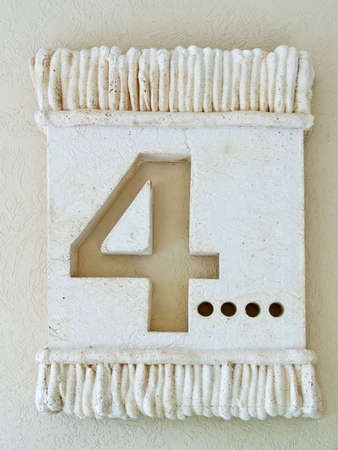 Number 4 barelief in stone. Old-fashion decoration on a wall. Standard-Bild