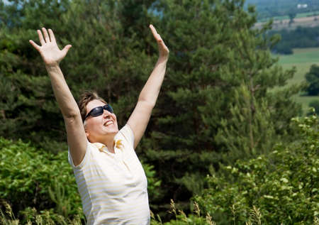 Woman with arms outstretched standing on the hill. Green forest on background. Summer.