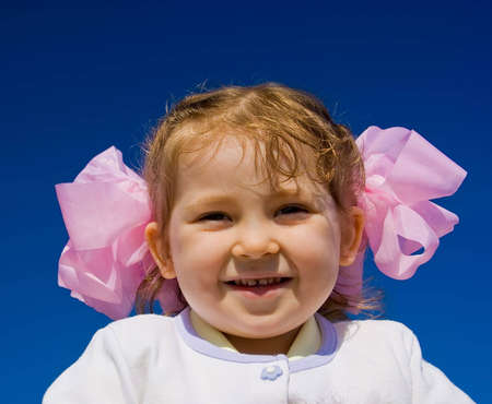 Cute smiling girl on blue sky background 免版税图像