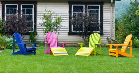 Multi-coloured chairs on front yard. Country side. Ontario, Canada.
