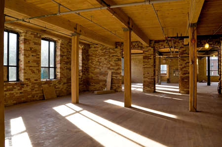 wooden beams: Old brick building is under reconstruction for modern office spaces.