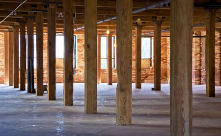 Construction site. Old brick building is under reconstruction for modern office spaces. Wood framing. Renovation.