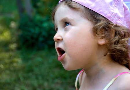 어린 소녀 감정입니다. 공원에서 귀여운 아가씨입니다. 녹색 잔디 배경입니다. 스톡 콘텐츠