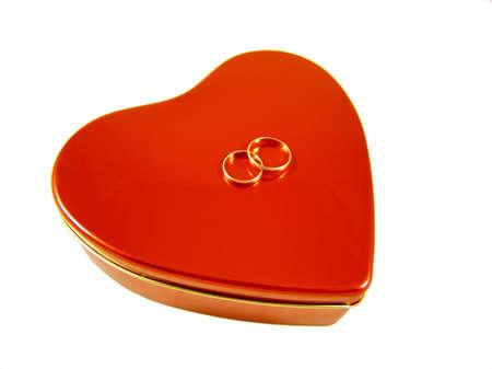 흰색 배경에 고립 된 두 개의 황금 반지와 빨간색 3 차원 심장 모양 상자. 발렌타인 인사말 카드를 위해 좋은입니다.