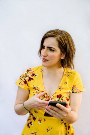 angry girl pointing her cellphone looking to the side with white background