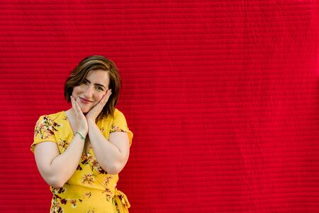 Tender young girl with hands on her face and yellow dress on red background