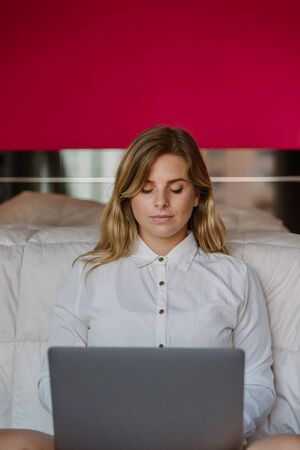 caucasian white blonde girl sitting with grey computer at the foot of the bed in bedroom, with closed eyes, breathing