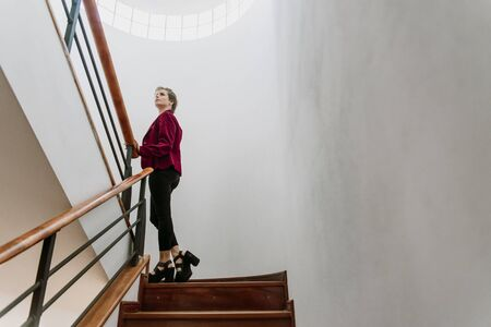 young, white, blond and beautiful businesswoman climbing stairs, with red jacket, black pants and high heels, view from below, looking up like growing up