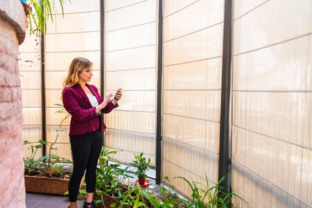 young caucasian woman with making a video call by cell phone, wearing formal clothes in the office with plants.