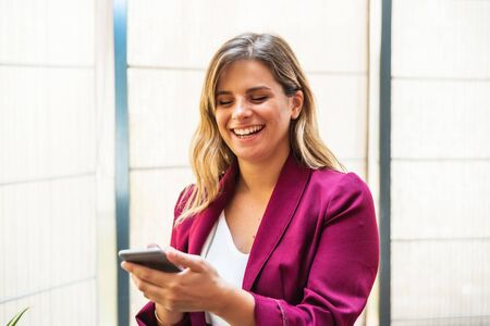 Happy young woman doing a video call with her mobile phone, laughing in the office. Imagens