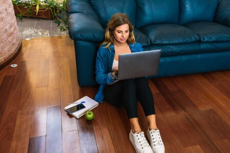 Stock photo of a caucasian woman sitting on the floor in front of her blue couch and typing on her laptop.