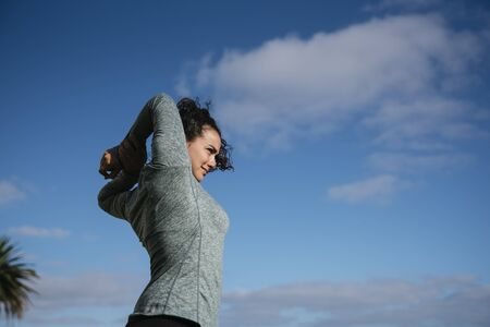 Stock photo of a caucasian woman wearing sportswear stretching her arms smiling and looking away from the camera.