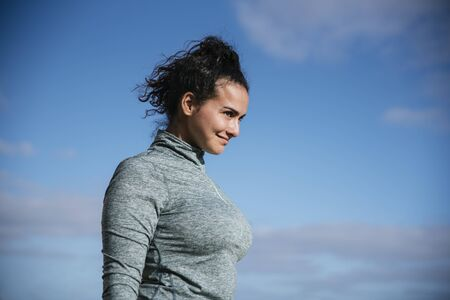 Stock photo of a caucasian woman wearing sportswear smiling and looking away from the camera.