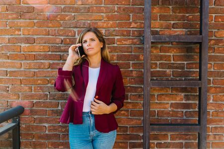 Stock photo of a caucasian woman talking on her mobile phone. She has her arm on her waist. She is standing next to a ladder. Foto de archivo