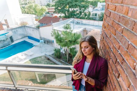Stock photo of a caucasian woman with her mobile phone. She is standing on a balcony. She is grabbing her hair.