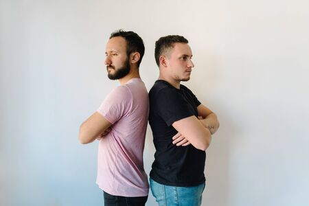 Stock photo of two caucasian men standing back-to-back. They both have their arms crossed and look displeased.