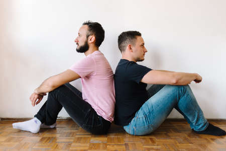 Stock photo of two caucasian homosexual men sitting back-to-back. They look angry.