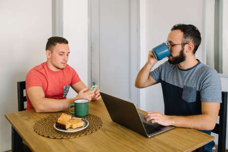 Stock photo of two caucasian adult men sitting at a table. One of them is working with a laptop and the other is helping him with his smartphone. Banco de Imagens