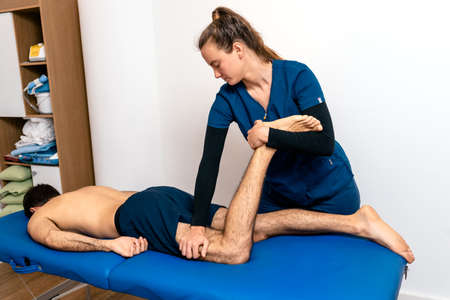 Stock photo of unrecognized man in physiotherapy clinic receiving massage.