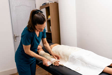 Stock photo of female worker in physiotherapy clinic wrapping patient's hand with bandage. Standard-Bild