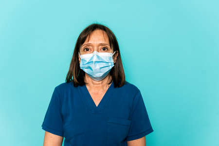 Stock photo of healthcare professional wearing face mask and disposable hair net looking at camera against blue background.