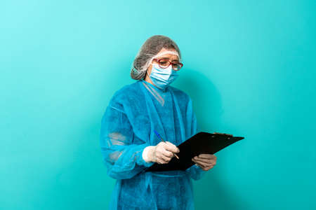 Stock photo of unrecognized healthcare worker wearing protective clothing taking notes against blue background. Stock Photo