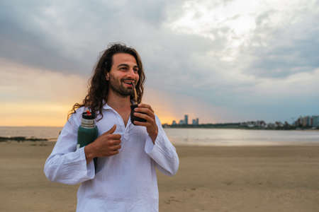 Stock photo of relaxed man with long hair smiling and drinking mate in the beach.